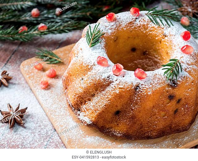 Christmas cake in the shape of a wreath with Christmas decorations. Pomegranate anise star fir-tree branches