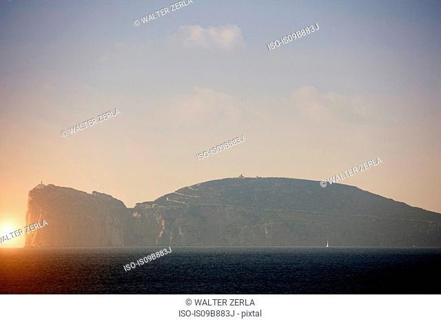 Hazy coastal view with cliff top lighthouse, Capo Caccia, Sardinia, Italy