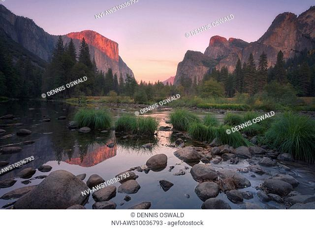 Yosemite Valley, El Capitan with alpine glow and reflection in Merced River in the Yosemite National Park, California, USA