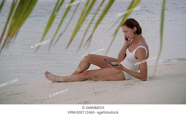 Young woman on beach using mobile and notebook