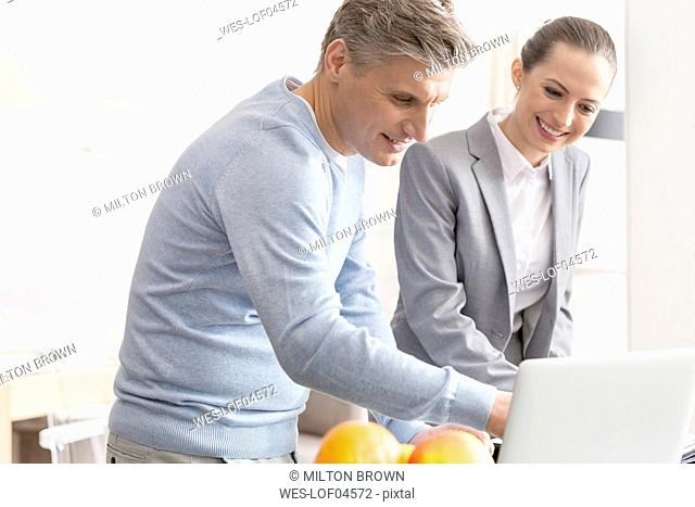 Smiling man and businesswoman using laptop together