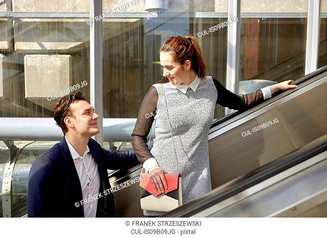 Businesswoman and businessman talking on escalator, London, UK