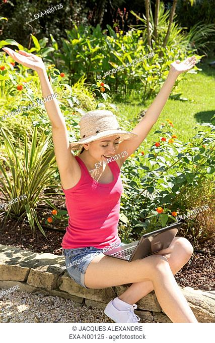 happy young woman using laptop in garden