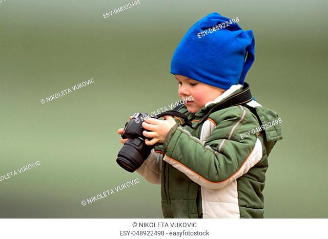 The little boy photographer is holding in hands a camera on green background