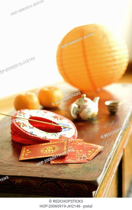 Chinese lantern and a kettle with envelopes on the table