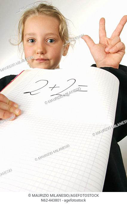 Little girl in elementary schools with indecisive expression with one hand shows the number three while the other holds a notebook on which there is written two...