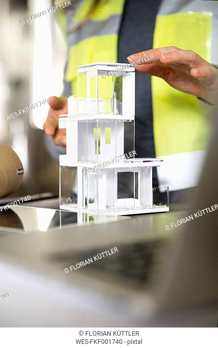 Close-up of woman wearing reflective vest with architectural model