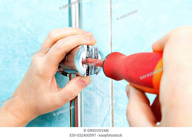 Repair of bathroom, closeup plumbers hand tighten the screw adjustable shower handle bracket using a screwdriver