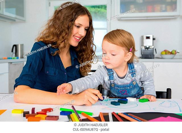 Teenage girl and female toddler drawing at kitchen table