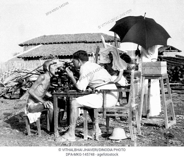 Leper patient Parchure Shastri being examined by an outside medical doctor at Sevagram Ashram , 1940 NO MR