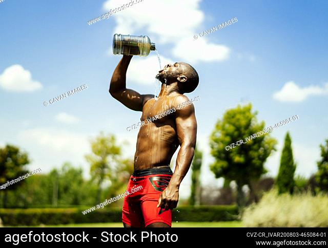 young athlete drinking water after playing sports