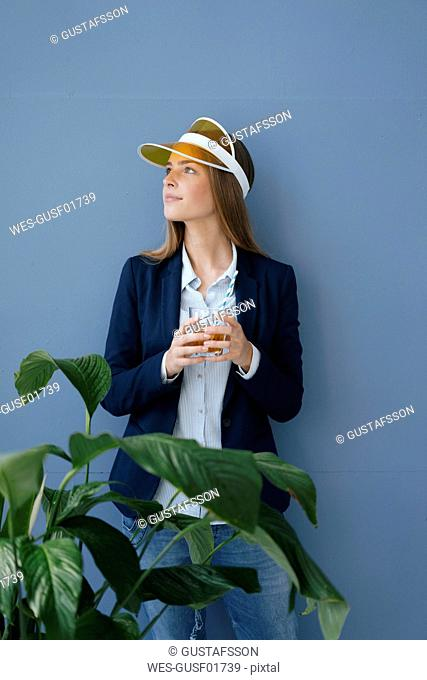 Portrait of a young businesswoman against blue background, dreaming of a holiday