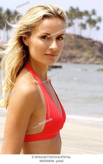 Portrait of beautiful blonde woman in red bikini top on a beach in India