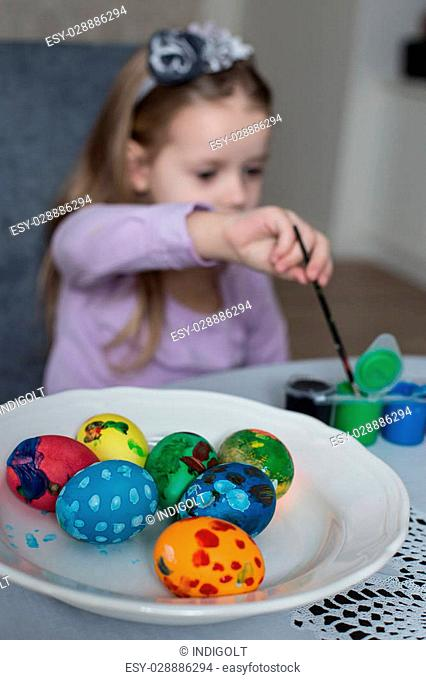 A happy little girl coloring easter eggs. Cozy home atmosphere. Easter
