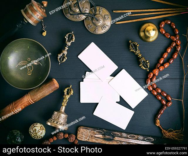 empty white business cards in the midst of Asian religious objects for meditation and alternative medicine on a black wooden background, top view