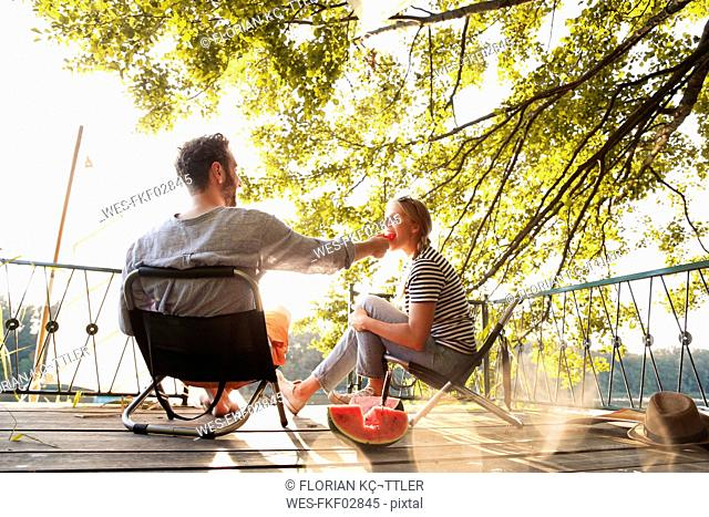 Young couple sitting on a jetty at a lake eating watermelon