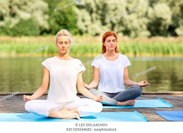 fitness, sport, yoga and healthy lifestyle concept - women meditating in lotus pose on river or lake berth