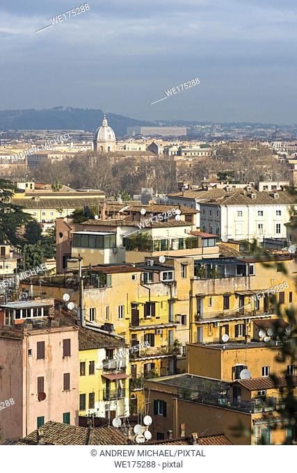 Views across Rome city with colourful old apartments in foreground, seen from Gianicolo or Janiculum Hill, Trastevere, Rome, Italy