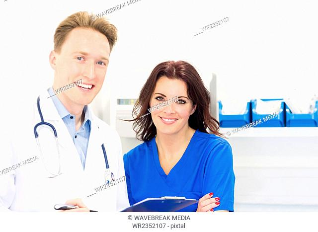 Portrait of happy veterinarians with clipboard