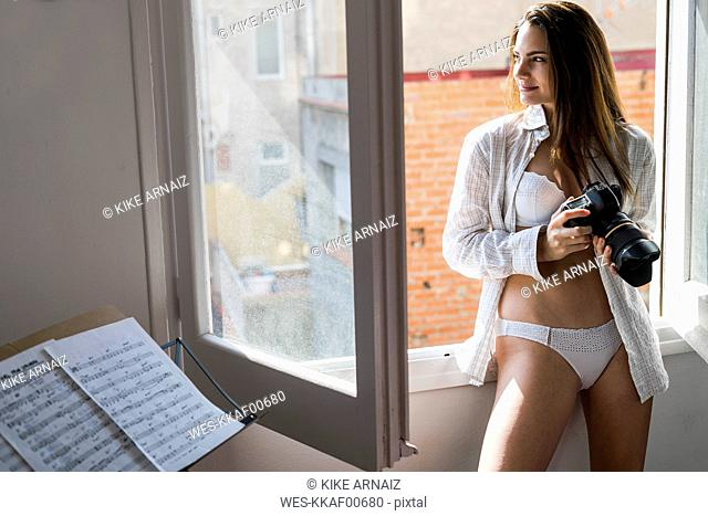 Smiling young woman with camera standing in front of open window