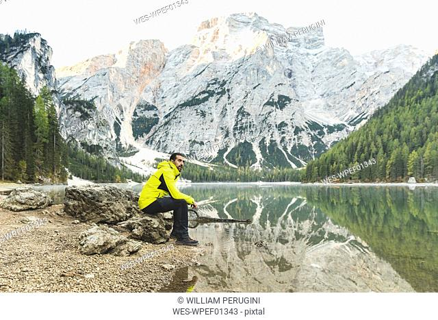 Italy, Braies Lake, man sitting on a rock at the lakeside with mountains and forest in background