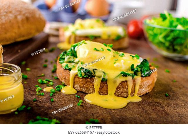 Egg benedict - rustic bread with poached egg and garlic spinach, topped with delicious hollandaise sauce