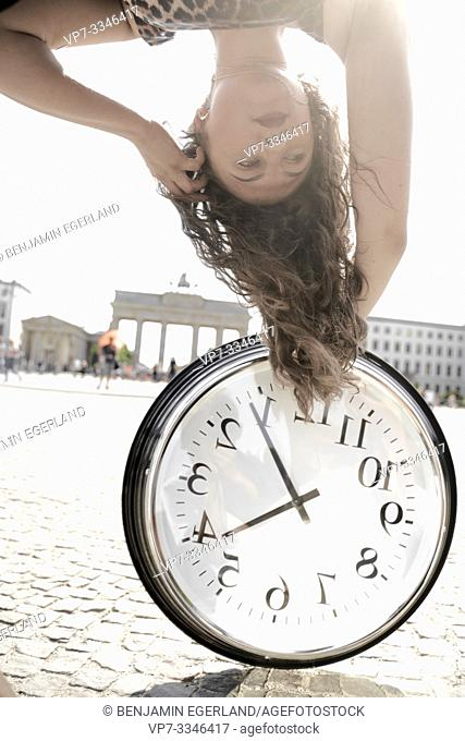 young emotional woman upside down with clock at street next to touristic sight Brandenburger Tor, Brandenburg gate, in Berlin, Germany