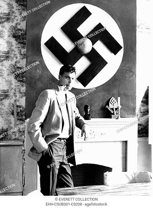 American Nazi George Lincoln Rockwell stands by a huge swastika on the wall over the fireplace. Running for Governor of Virginia, he said