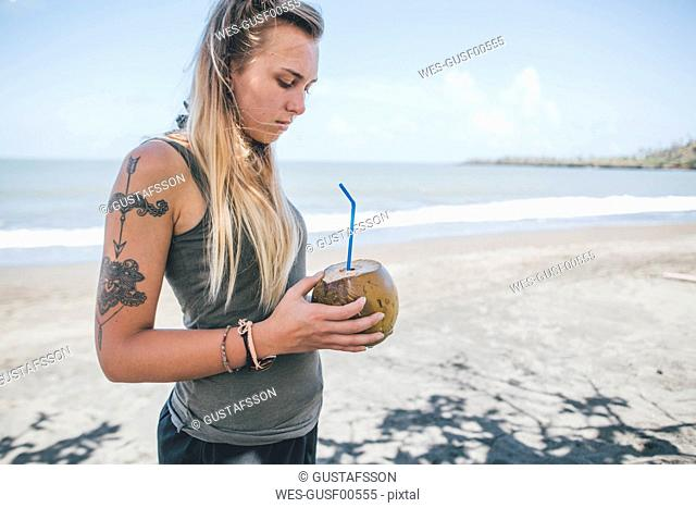 Cuba, Young woman with tattoo at Playa de Miel drinking coconut water