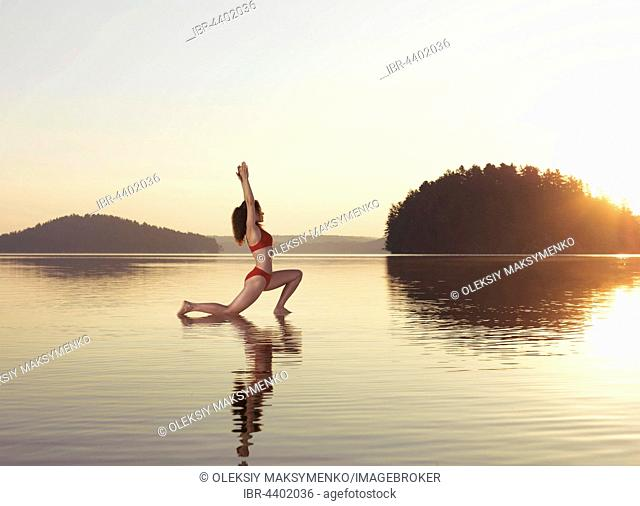Young woman practicing Hatha yoga on a floating platform in water on a lake during a misty sunrise, Yoga Low Lunge posture, Anjaneyasana