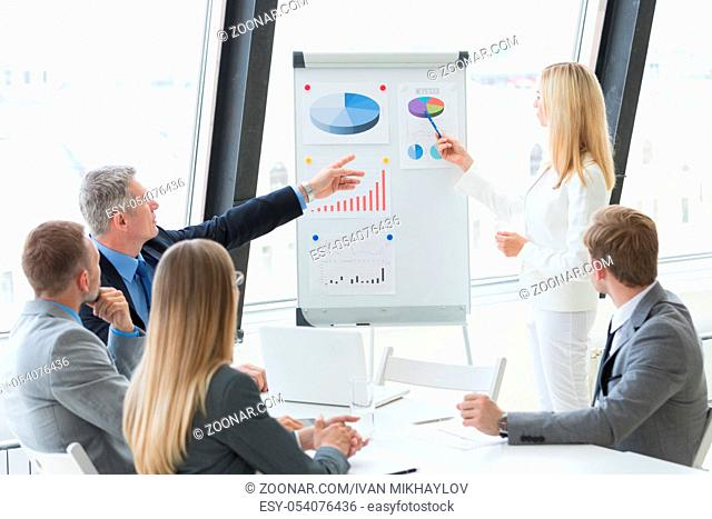 Business people team at presentation in office working with charts and diargams at flipchart
