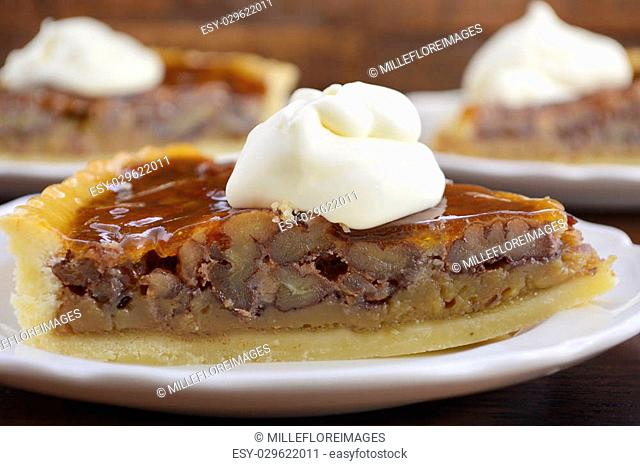 Traditional Thanksgiving individual serving of pecan pie on dark wood rustic wood table and background, closeup