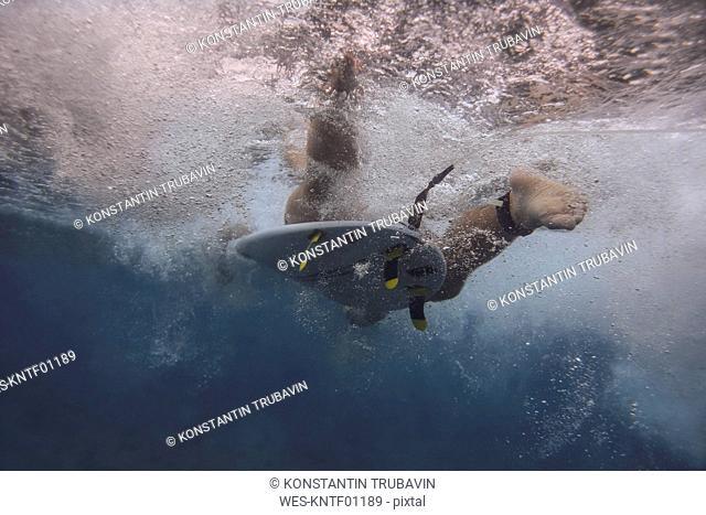 Maledives, Indian Ocean, surfer on surfboard, underwater shot