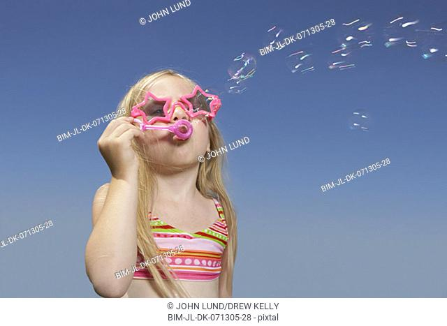 Young girl in fancy sunglasses blowing bubbles