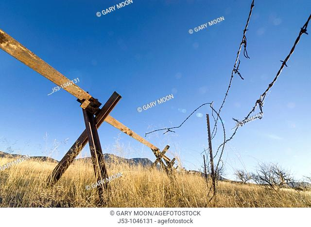 Cut barbed wire and steel 'vehicle barrier' on United States /Mexico border, east of Nogales, Arizona, USA, looking northeast into US