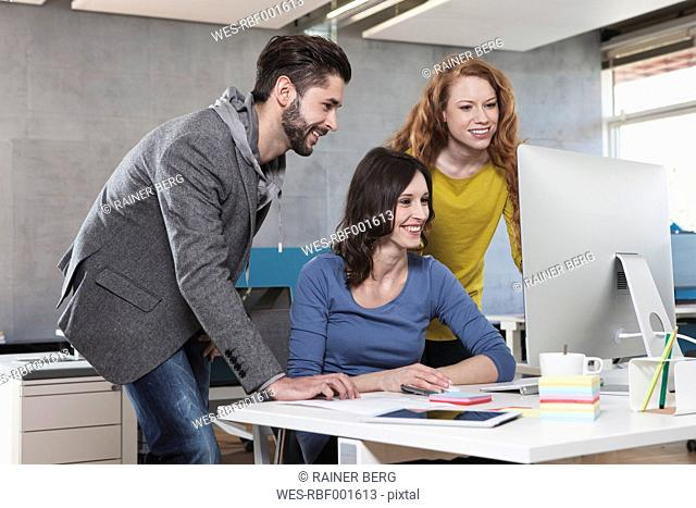 Three colleagues looking at computer in the office