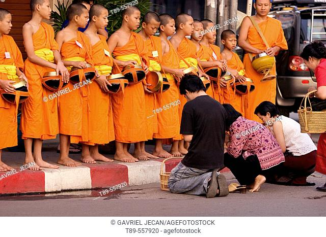 Asia, Thailand, Chiang Maik, Buddhist monk collects offerings of food and flowers each morning