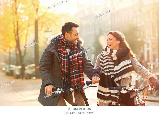 Smiling young couple in warm clothing bike riding on urban autumn street