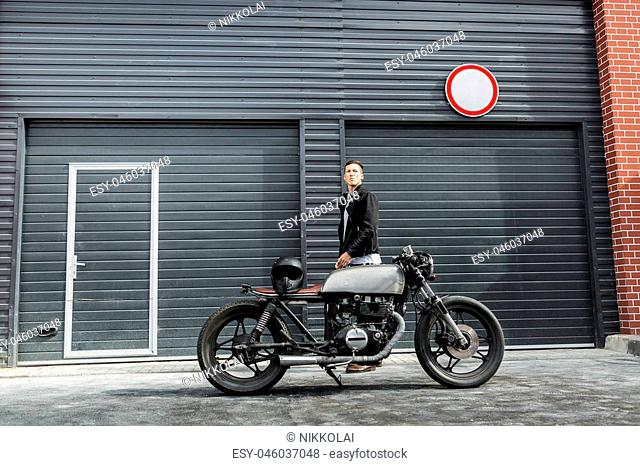 Handsome rider man in black leather biker jacket ready for travel on classic style cafe racer motorcycle industrial gates as background