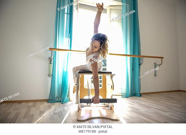Woman Exercising on Pilates Machine Against a Window With Sunlight in Switzerland