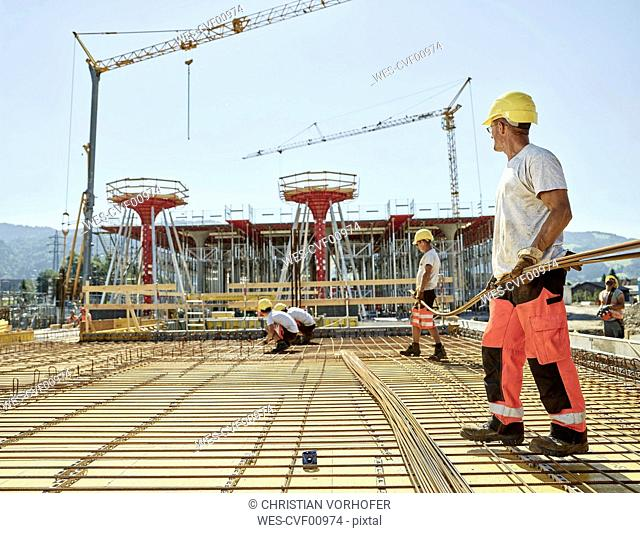 Workers on construction site preparing iron rods