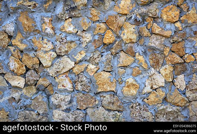 wall of yellow stones of different sizes fastened with gray cement, full frame