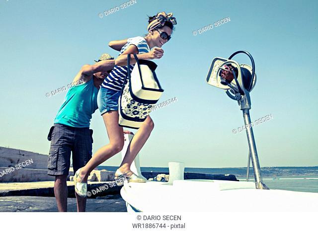 Croatia, Dalmatia, Young couple at the seaside, entering a boat