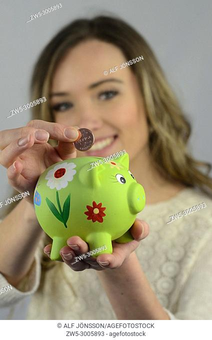 Young woman put a con in a piggy bank