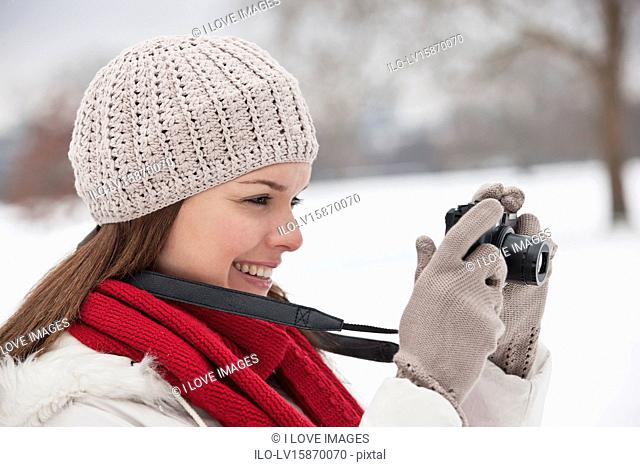 A young woman standing in the snow, taking a photograph