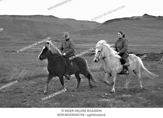 Two people horseriding