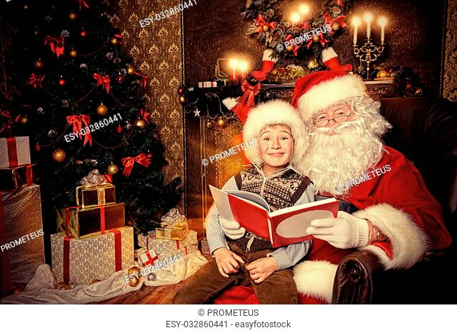 Santa Claus and happy boy sitting in Christmas room and reading a book. Christmas home d?cor