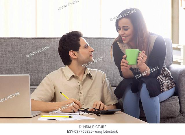 Couple discussing home finances with paper and laptop