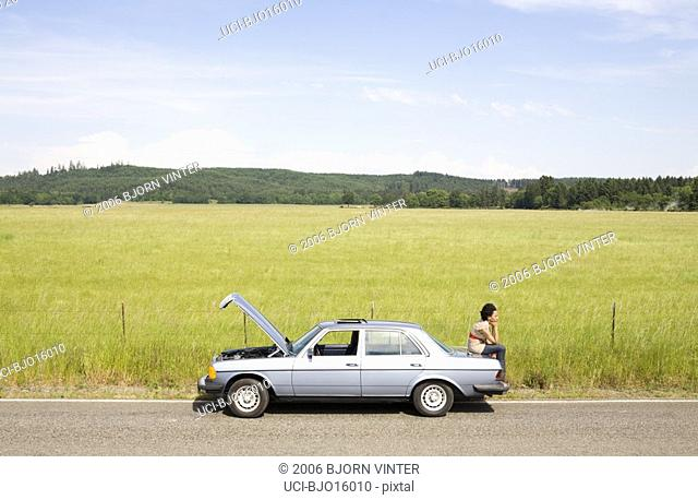 Woman sitting on trunk of broken down car
