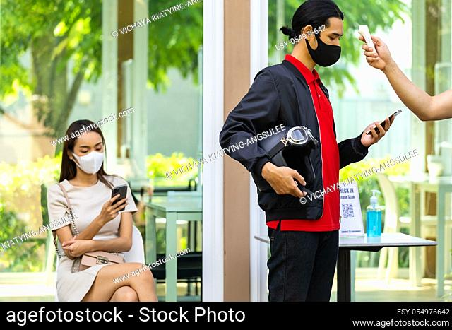 Take Temperature for customer with face mask before getting in restaurant with social distance queue in line new normal after coronavirus covid-19 pandemic